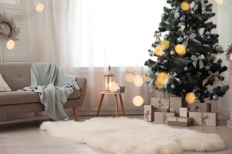 Stylish living room interior with decorated Christmas tr. Ee and blurred lights in foreground royalty free stock photo