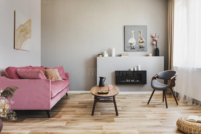 Stylish living room interior with pastel pink sofa, wooden coffee table and eco fireplace. Stylish living room interior with pastel pink sofa, wooden coffee stock photography