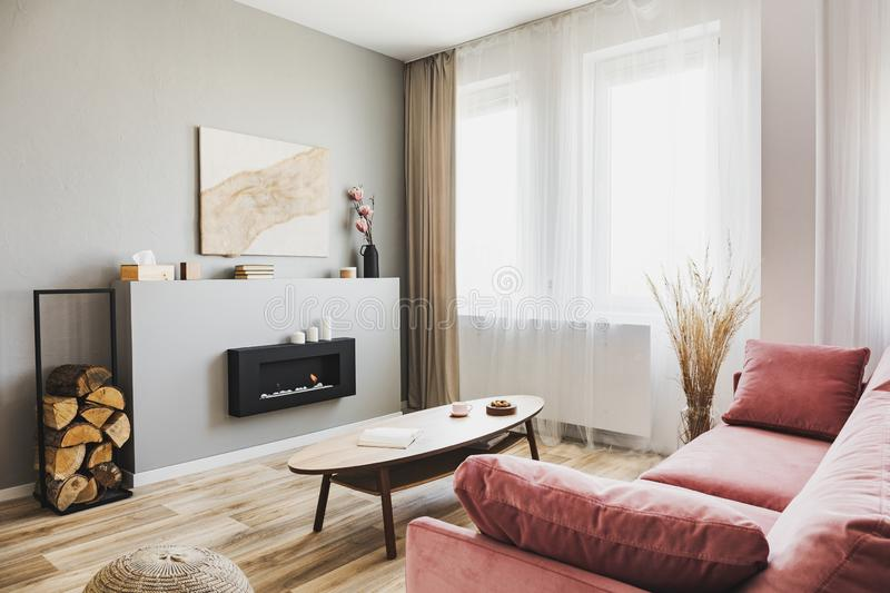 Stylish living room interior with pastel pink sofa, wooden coffee table and eco fireplace. Stylish living room interior with pastel pink sofa, wooden coffee stock image
