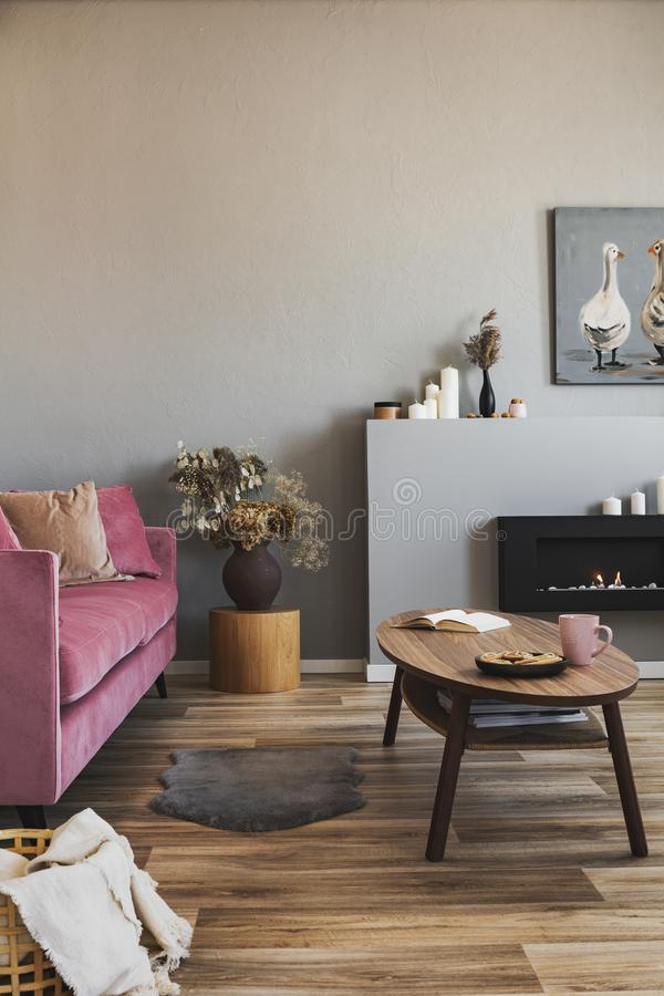 Stylish living room interior with pastel pink sofa, wooden coffee table and eco fireplace. Stylish living room interior with pastel pink sofa, wooden table and royalty free stock images