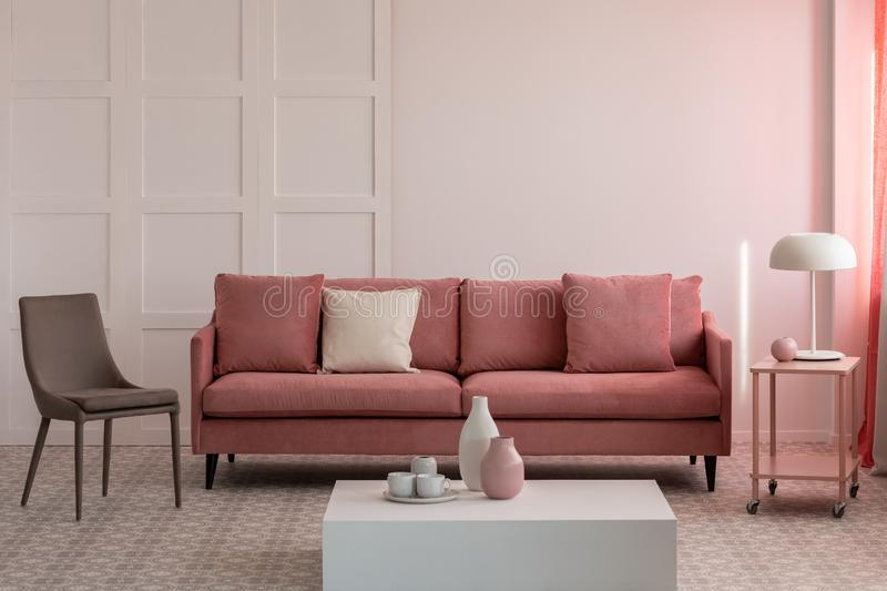 Stylish living room interior with pastel pink velvet sofa. With pillows and trendy grey chair royalty free stock photo