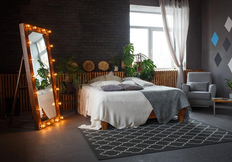 Stylish loft cozy living room with double bed, carpet, armchair, green plants and geometrical patterns on the wall. Stylish loft living room with double bed stock image