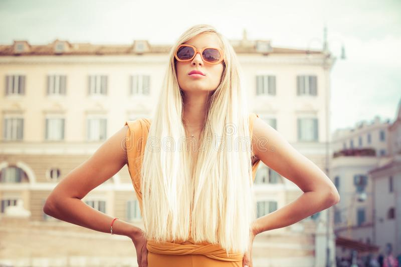 Stylish long blond hair young woman with sunglasses in the city. Stylish long blond hair young woman with sunglasses and orange dress in the city. Confident royalty free stock photography
