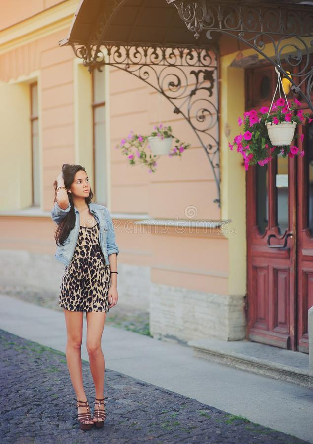 Stylish long hair brunette woman in a leopard animal print dress with sexy legs in brown high heel shoes, denim jacket stock photos