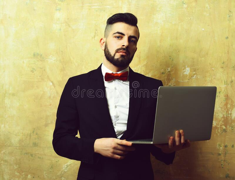 Stylish looking bearded businessman with confident face expression holds laptop stock image