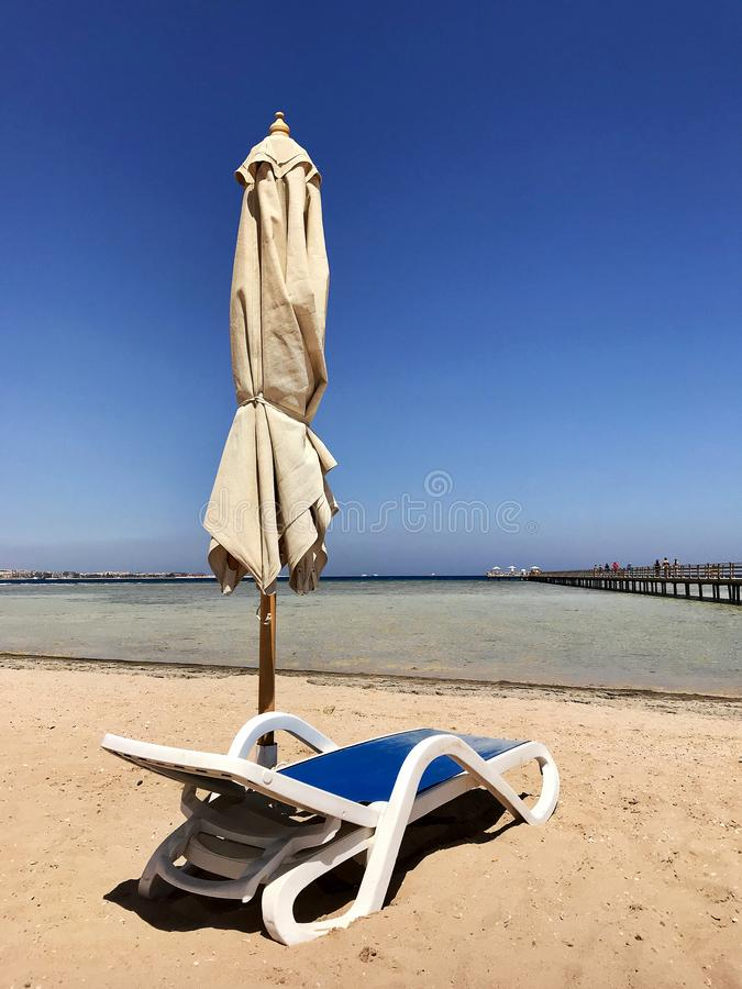 Stylish lounger in yellow sand to sun sunbed on beach in summer under open sky stock photography