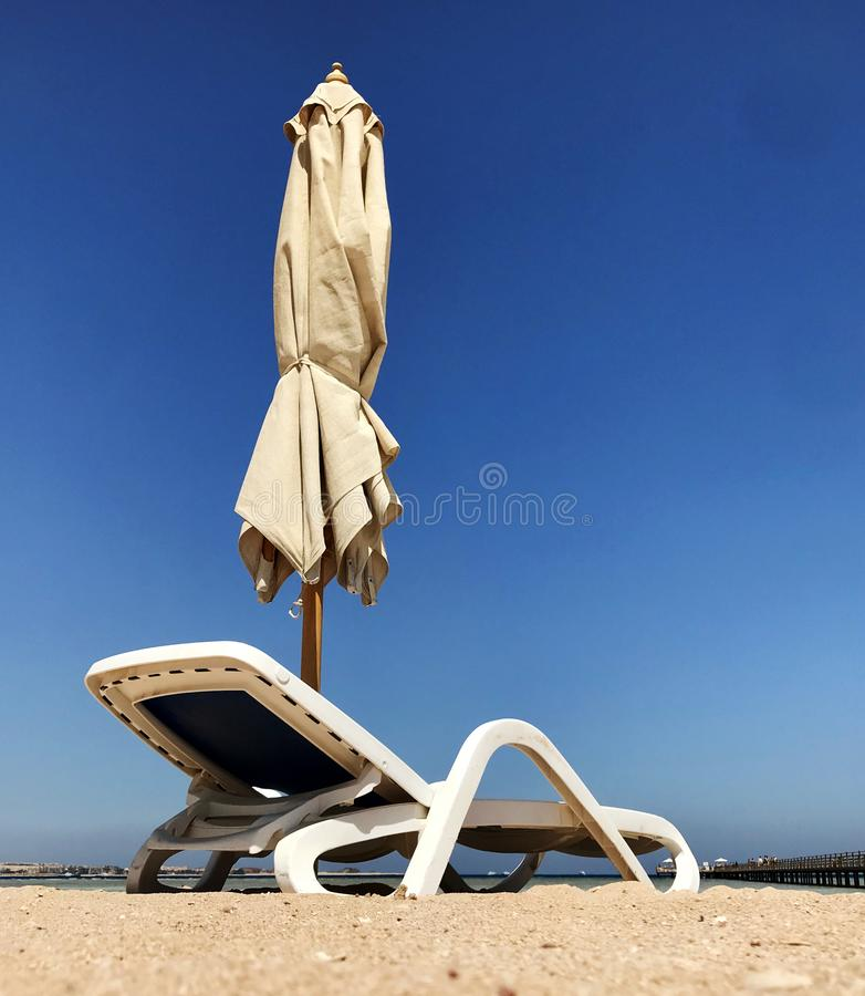 Stylish lounger in yellow sand to sun sunbed on beach in summer under open sky royalty free stock photography
