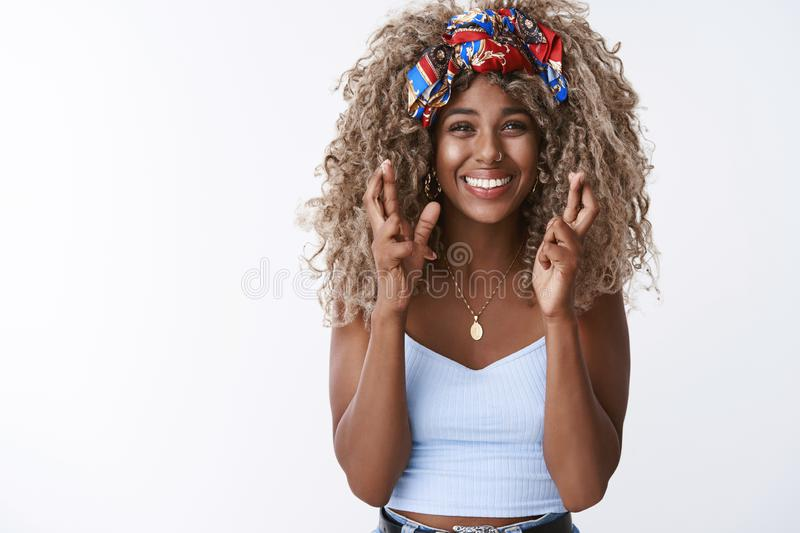 Stylish and lovely african-american curly-haired woman afro hairstyle, believe dreams come true, feeling luck her side. Cross fingers good fortune, smiling stock images