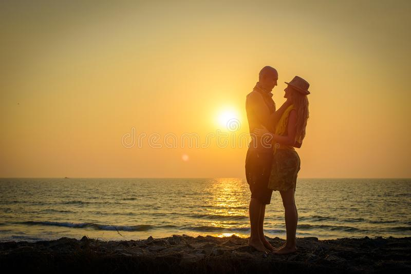 Stylish loving couple hugging each other on the beach at sunset. Man and woman in holiday honeymoon trip royalty free stock images
