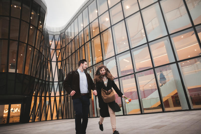 Stylish loving couple kissing and hugging near modern building royalty free stock photography
