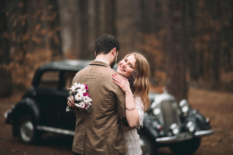 Stylish Loving wedding couple kissing and hugging in a pine forest near retro car.  royalty free stock images
