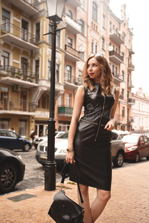 Stylish, luxurious girl in a chic black dress on the street, female with fashion makeup near the building, black dress on tall stock image
