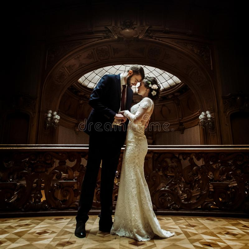 Stylish luxury bride and handsome elegant groom posing on the ba royalty free stock images