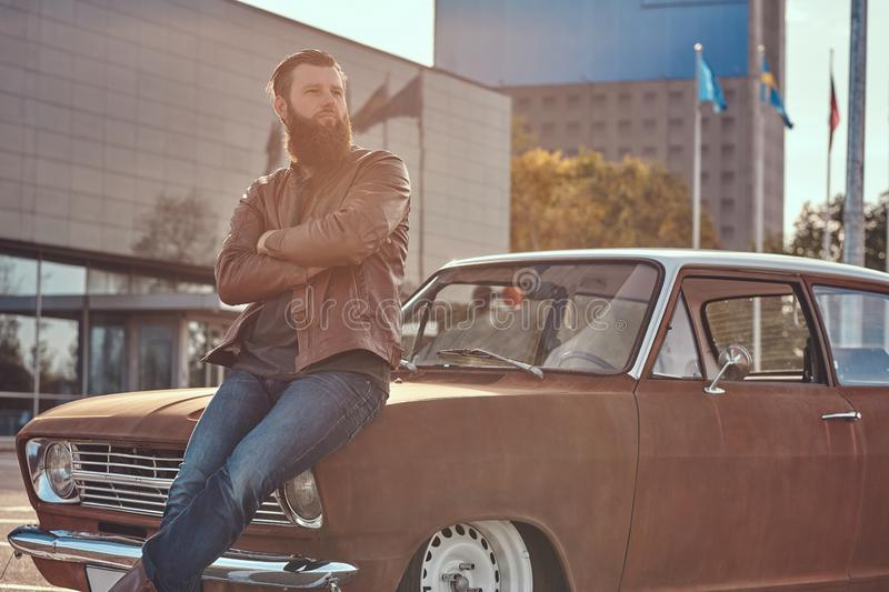 Stylish male leaning on tuned retro car in the city parking near skyscraper at bright sunset. royalty free stock photos