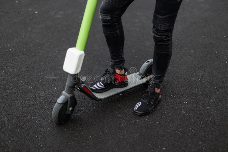 Stylish male legs in black jeans in trendy black sneakers on a electric scooter on a summer day. Fashionable guy stands. On a asphalt near a modern scooter stock image