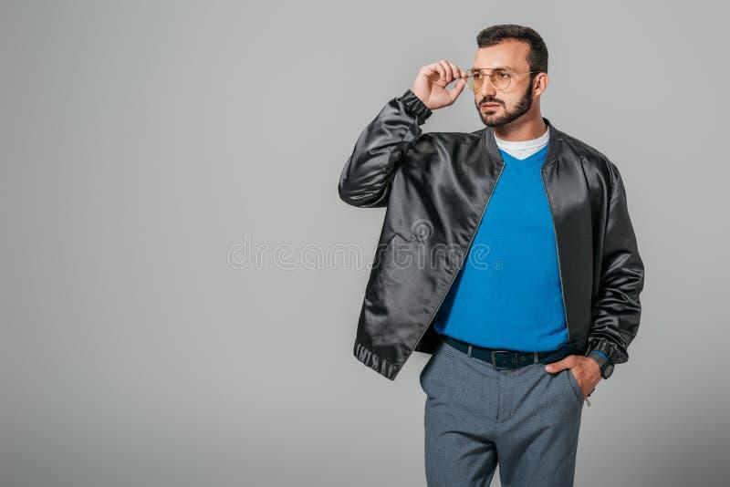 Stylish male model adjusting eyeglasses and looking away. Isolated on grey background royalty free stock image