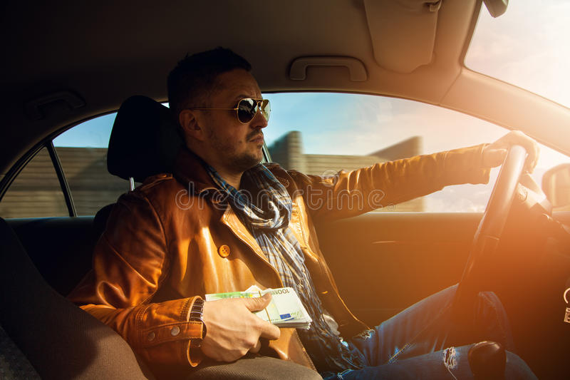 Stylish male model holding a lor of money EUR and driving car. Inside photo stock image
