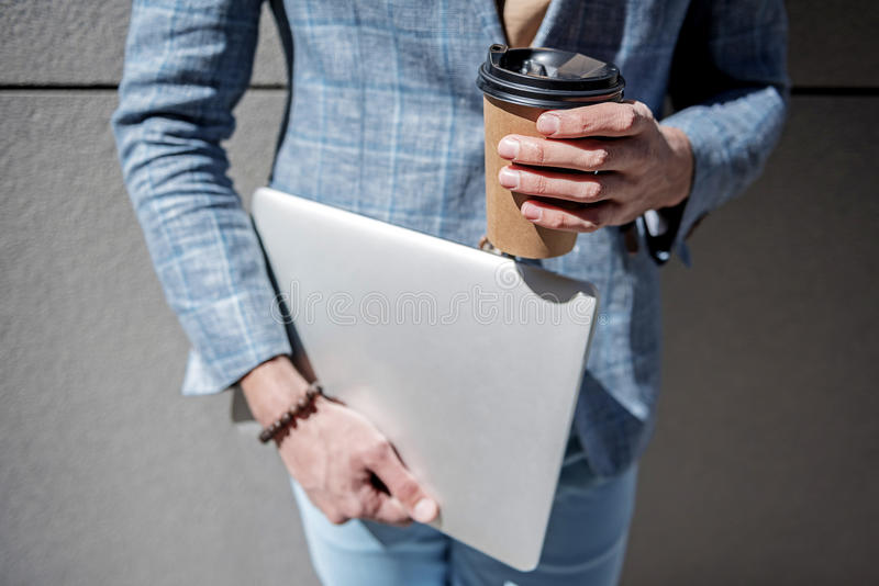 Stylish male person having break. Elegant man is holding modern laptop and cup of coffee. Focus on necessary things for active businessman. Close up stock image