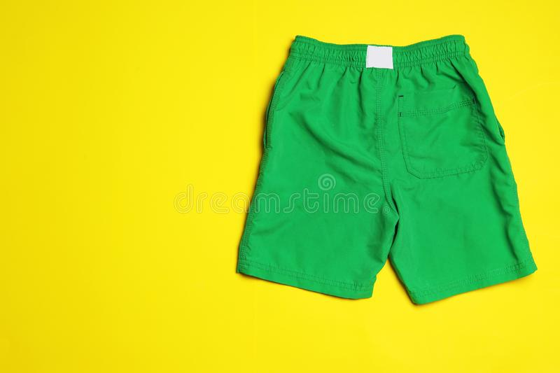 Stylish male swim trunks on color background, space for text. Beach object. Stylish male swim trunks on color background, top view with space for text. Beach royalty free stock images