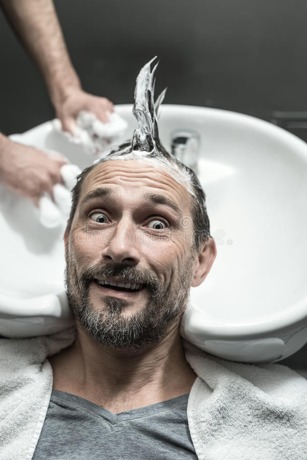 Stylish man in barbershop. Funny men with a beard lies on the white sink in the barbershop. He has the lathered head with the punk hairstyle. Guy looks to the stock images