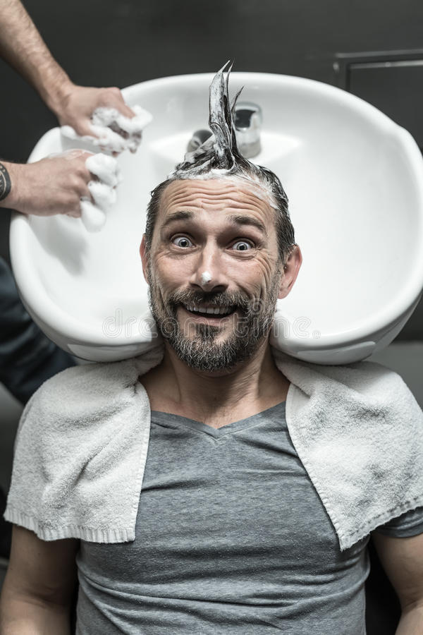 Stylish man in barbershop. Grimacing men with a beard lies on the white sink in the barbershop. He has the lathered head with the punk hairstyle. Guy wears a stock photos