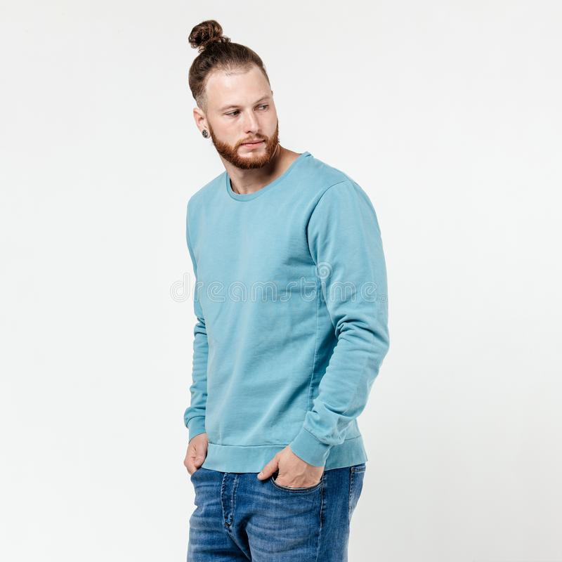 Stylish man with beard and bun hairstyle dressed in light-blue long sleeve sweater and jeans poses in the studio on the stock images