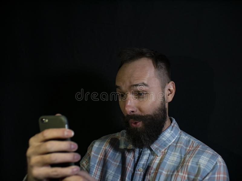 Stylish man with a beard and mustache looks into a mobile phone with a surprised face on a black background royalty free stock photo