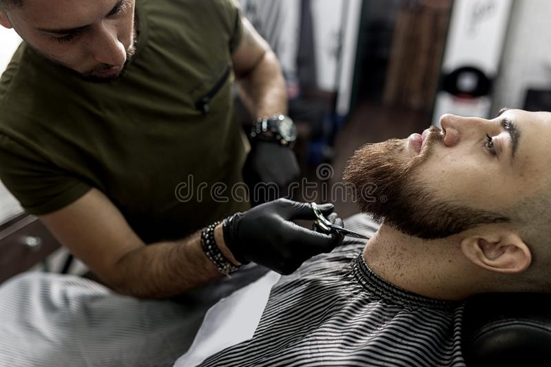 Stylish man with a beard sits at a barbershop. Barber trims mens beard with scissors. royalty free stock photography