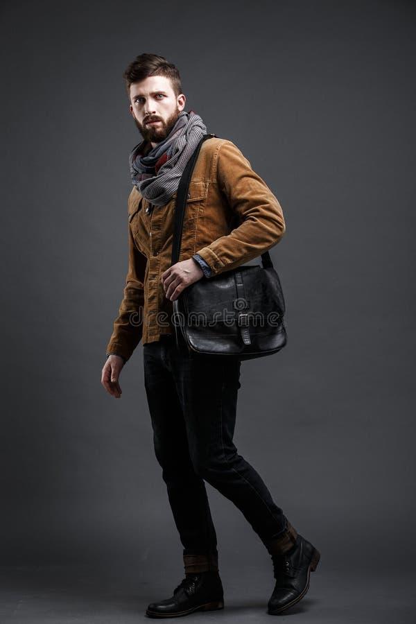 Stylish man with black leather bag. Portrait of bearded man with leather bag and stylish clothes looking up.Studio shot.Isolated stock image