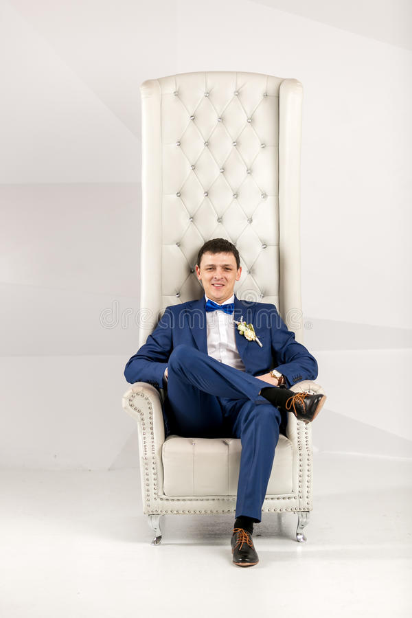 Stylish man in blue suit posing in white armchair at studio royalty free stock photos