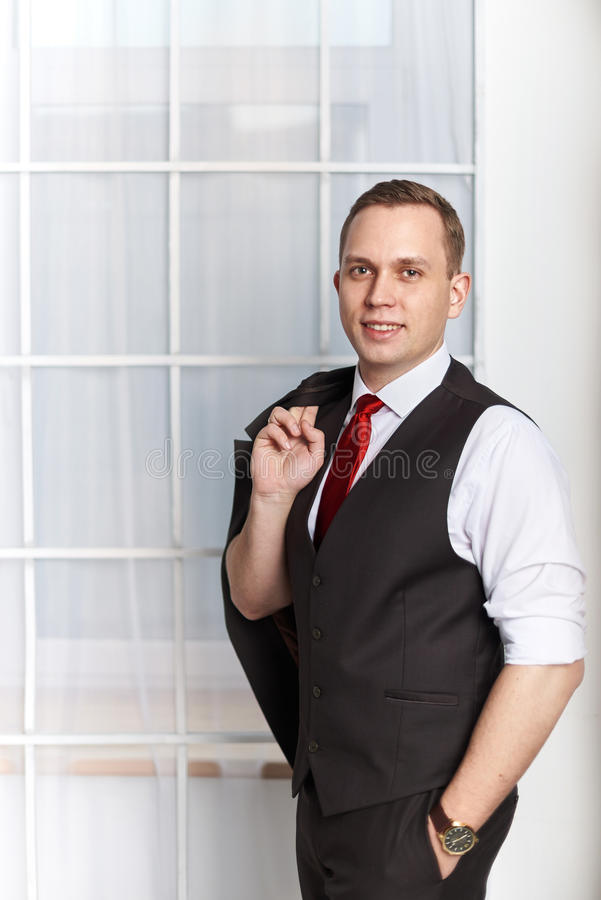 Stylish man businessman groom. In black smoking with a red tie stock image