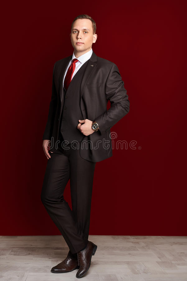 Stylish man businessman groom. In black smoking with a red tie stock photos