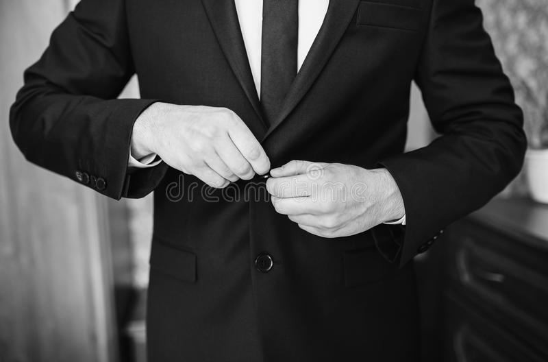 Black and white art monochrome photography. A stylish man in a dark jacket. The businessman in a respectable suit button up his buttons stock photos