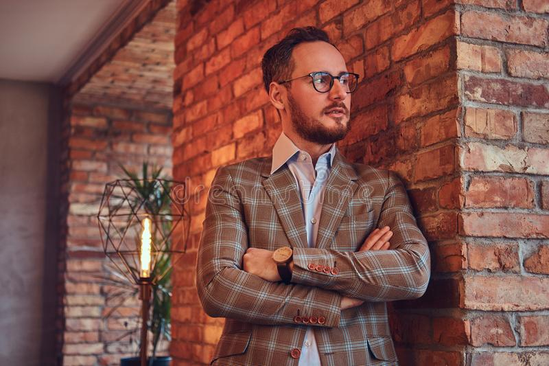 Stylish man in a flannel suit and glasses leaning against a brick wall in a room with loft interior. royalty free stock image