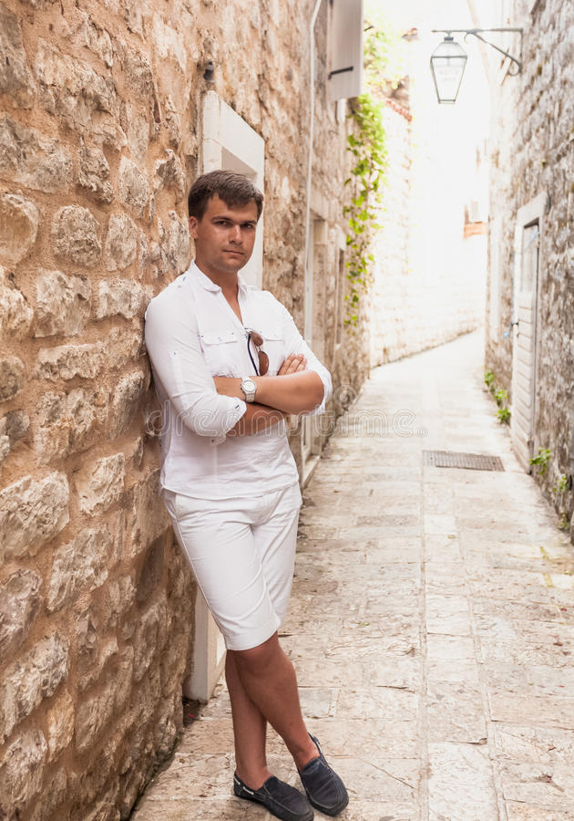 Stylish man leaning against old stone wall on street. Handsome stylish man leaning against old stone wall on street royalty free stock images