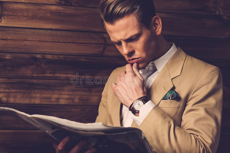 Stylish man with newspaper. In rural cottage interior royalty free stock photos