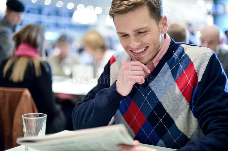 Stylish man reading newspaper at cafe. Young man sitting at table in cafe, reading newspaper royalty free stock image