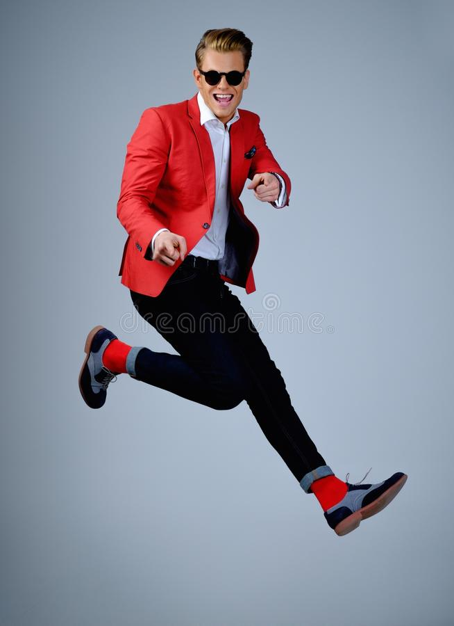 Stylish man in red jacket. Having fun jumping royalty free stock photos