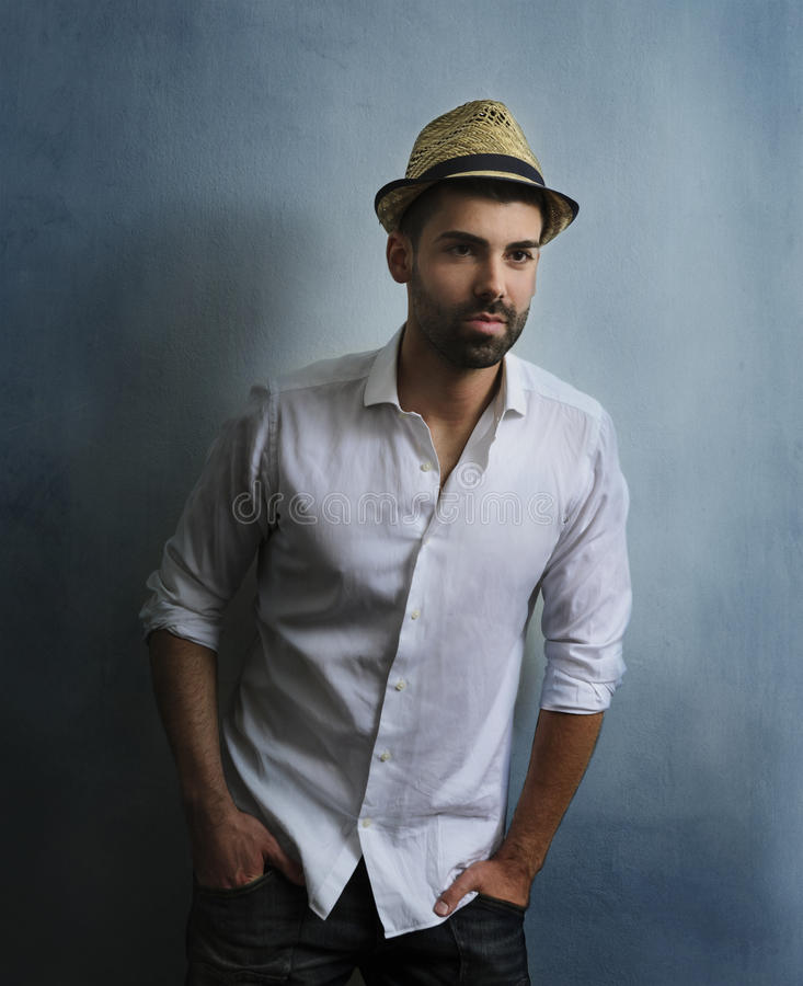 Stylish man with retro hat. Young hipster guy with beard posing in front of blue grunge wall. Portrait of stylish male model with retro hat and casual style royalty free stock images