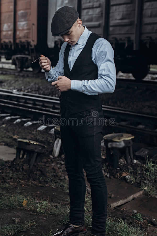 stylish man in retro look smiling posing on background of railway. england in 1920s theme. fashionable brutal confident gangster. royalty free stock images