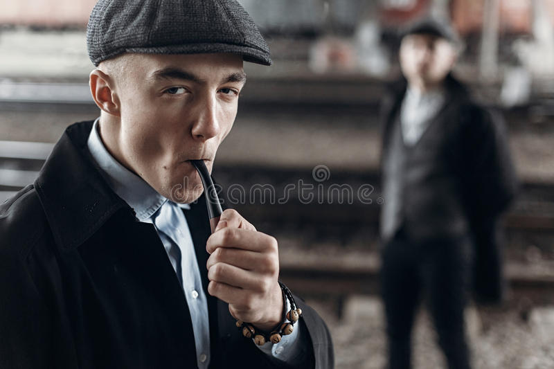 Stylish man in retro outfit, smoking wooden pipe. sherlock holmes look. england in 1920s theme. fashionable confident gangster. Stylish men in retro outfit royalty free stock photo