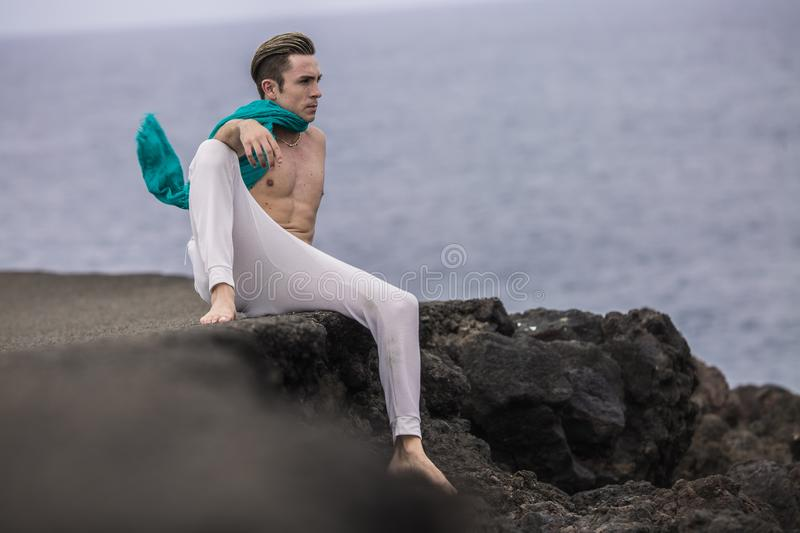 Stylish man sitting in relaxed pose on cliff. Thoughtful fashion man with nude torso in comfortable white pants sitting hanging leg down on stony cliff and stock photos