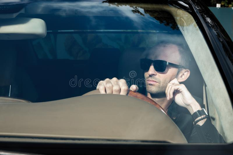 Stylish man in suit in black car. Business Man in glasses sitting in luxury auto. Success people. Millionaire gangster stock photos