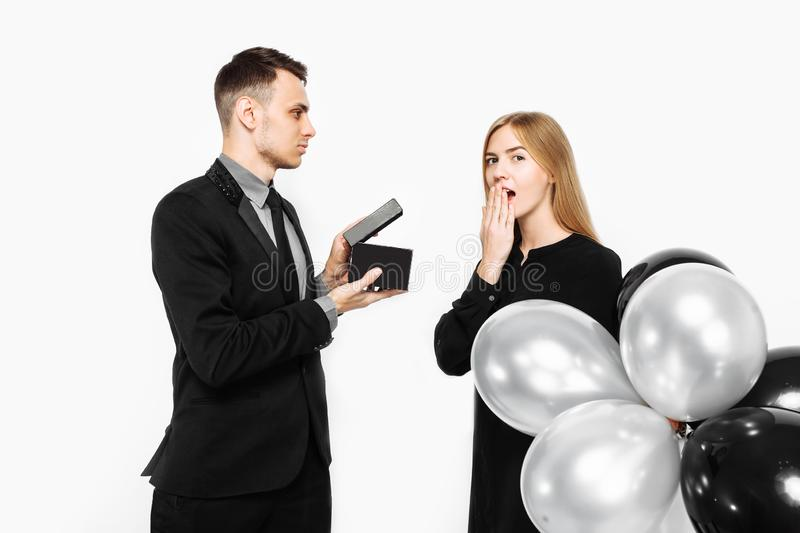 Stylish man in a suit makes a proposal for marriage to a girl who is shocked, a man holds a box with a gift in his hands in front stock photography