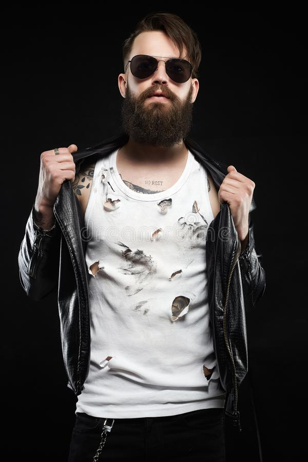 Stylish man with tattoo, sunglasses, beard. Fashionable hipster man. Brutal bearded boy in glasses and leather coat royalty free stock image