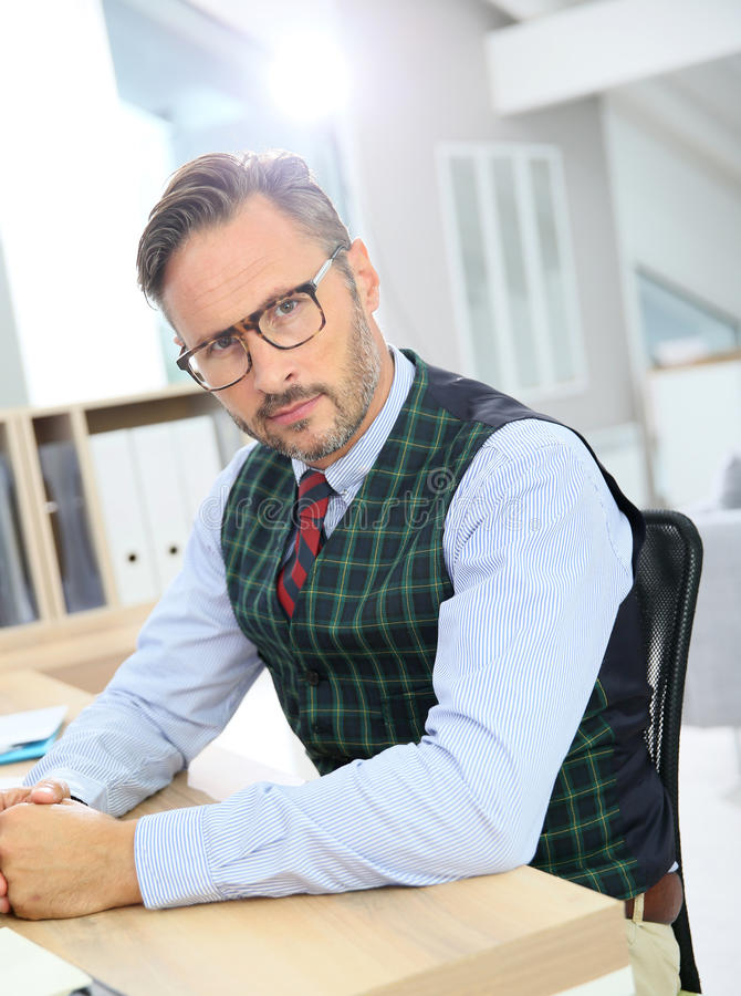 Stylish man wearing eyeglasses and working. Stylish man with eyeglasses sitting in office stock photos