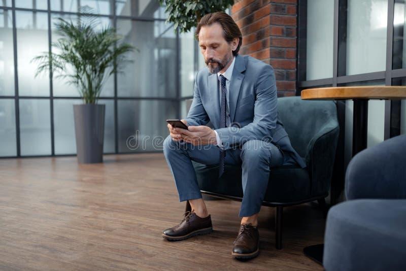 Stylish mature businessman typing message on smarpthone. Typing message. Stylish mature businessman wearing grey suit typing message on smarpthone stock image