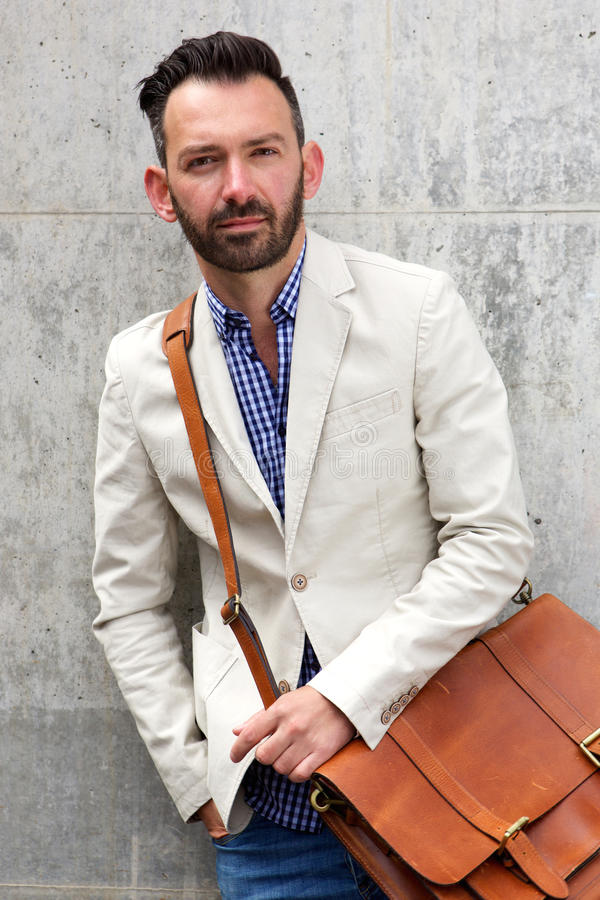 Stylish mature man with leather shoulder bag. Portrait of stylish mature man with leather shoulder bag standing against wall royalty free stock photos