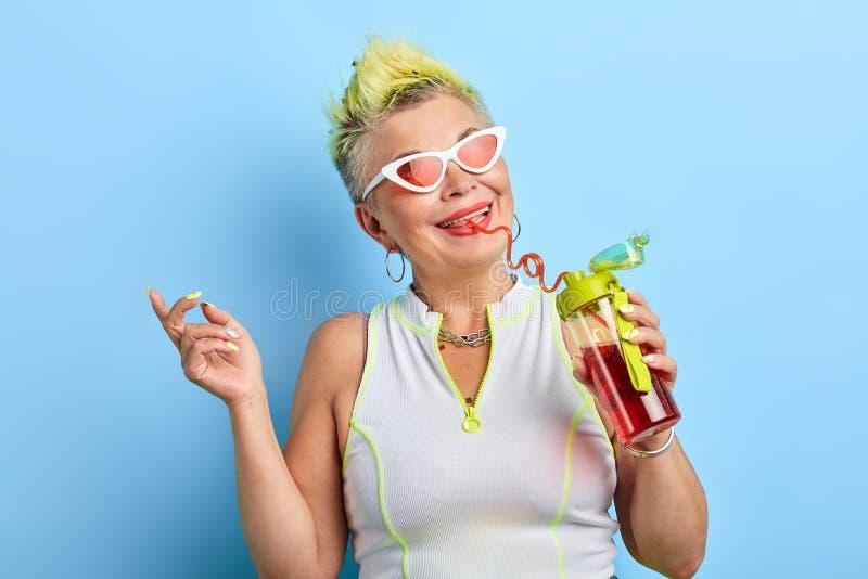 Stylish mature woman enjoying lifestyle. Stylish mature woman with yellow dyed hairstyle enjoying lifestyle, closeup portrait, isolated blue background, studio royalty free stock images