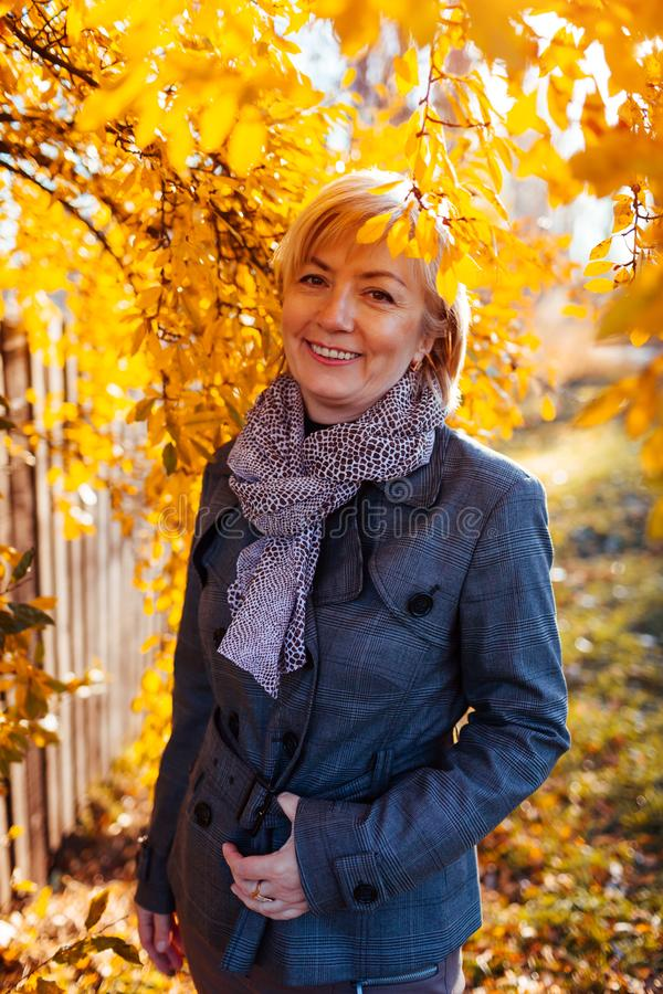 Stylish middle-aged woman posing in autumn park. Senior lady wearing fall clothes and accessories stock photo